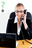 Ambitious businesswoman talking on phone using her laptop in the office