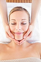 Happy woman receiving a head massage in a spa centre