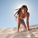 Pretty woman kneeling in sand