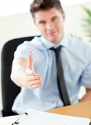 Self_assured businessman reaching his hand to the camera in his office