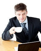 Charismatic businesman drinking coffee using his laptop at the breakfast table