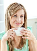Charming young woman enjoy her coffee sitting in the kitchen at home