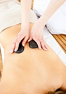 Close_up of a young woman receiving a back massage with hot stone in a health spa