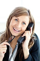 Confident young businesswoman talking on phone sitting in her office