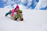 Laughing couple sledding down ski slope together