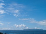 Blue sky over tranquil ocean with land in background