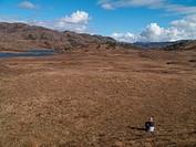 Hiker sitting in remote field under blue sky