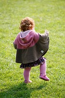 Rear of a one year old baby/toddler learning how to walk in a park