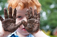 A five year old boy playing in mud in his garden