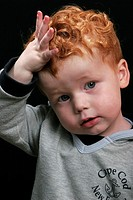 The face of a toddler with red hair, against black background