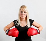 Boxing woman in red gloves and black top against white background  Blonde hair  Boxer