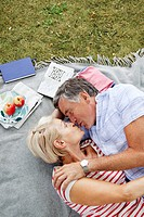 Mature couple kissing on picnicblanket