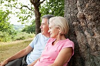 Mature couple sitting against tree
