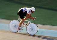Cyclist with speed helmet goes past on track in a blur