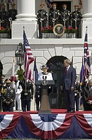 Queen Elizabeth II speaking with President George W. Bush to her left during the National Anthem on the South Lawn of the White House for the May 7, 2...