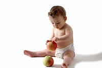 A baby playing with apples
