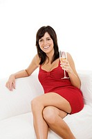 Beautiful Caucasian woman setting on a couch relaxing with a glass of white wine