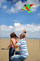 Portrait of family group flying a kite on beach