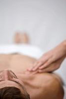 Close up of massage therapist hands massaging man shoulder