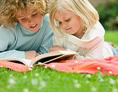 Two children lying in the garden reading a book