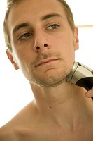 Young man shaving with electric razor