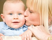 Close up of a smiling baby with his mother kissing him
