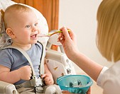 Baby sitting in his highchair with his mother feeding him