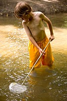 Young boy fishing in a river with fishing net