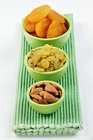 Dried apricots, sultanas and almonds in small bowls