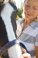 Mature woman standing next to a horse