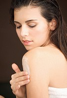 Woman applying body lotion over her shoulder