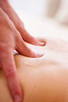 Extreme close up of a masseur hands on a woman back