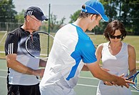 Tennis teacher instructing a couple