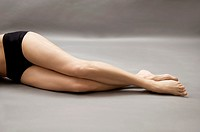 Woman lying on side with liposuction markings on her thigh, headless