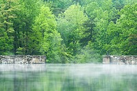 Mist hovering over a lake and a stone dam wall surrounded by spring green trees. Hanging Rock State Park.