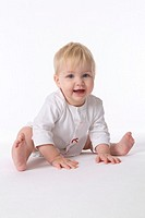 Happy Pliant Baby Girl Is Sitting On The Floor On White Background