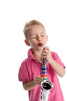 Little boy is playing a toy saxophone on white background