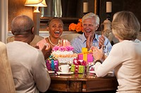 Smiling couples celebrating birthday with cake and gifts at dining room table