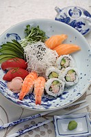 Variety of sushi rolls and sashimi in bowl