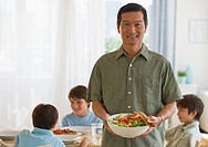 Smiling father holding salad with sons at table in background