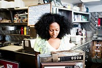 Mixed race waitress at cash register in diner