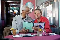 Black couple reading menu in restaurant