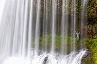 oregon, united states of america, a person with arms raised behind north middle falls in silver falls state park