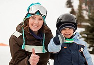 red deer, alberta, canada, a mother with her young son wearing helmets and ski masks giving the ´thumbs up´ sign