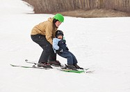 red deer, alberta, canada, a father and son skiing together on a hill