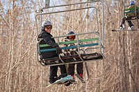 red deer, alberta, canada, a father and son on a chair lift at a ski area