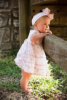 baby girl standing against a fence, nashville, tennessee, united states of america