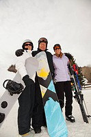 red deer, alberta, canada, three adults at a ski area holding snowboards and skis