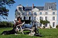 READING IN A DECKCHAIR IN FRONT OF THE CHATEAU DE LA PUISAYE, VERNEUIL_SUR_AVRE