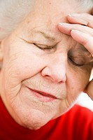 Tired elderly woman, with her eyes closed, resting her head on her hand.